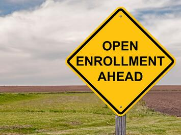 A photo of a yellow street sign advertising benefits open enrollment.