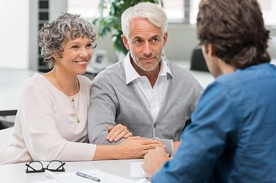 A photo of an older couple meeting with their financial advisor about their retirement options.