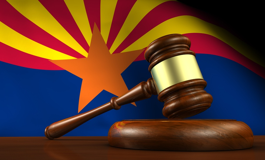 A photo of a judge's gavel in front of the Arizona state flag.