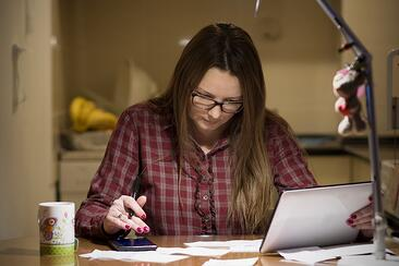 A photo of a woman paying bills after everyone else is in bed.