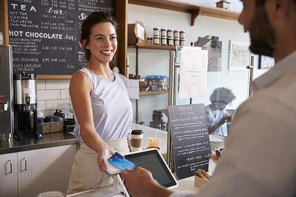 A photo of a coffee shop employee interacting with a customer.