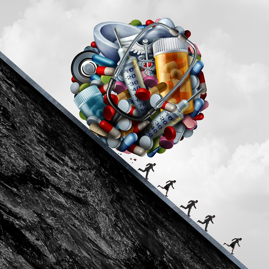 cartoon image of pills and syringes compacted into a ball rolling down a hill with people running away.