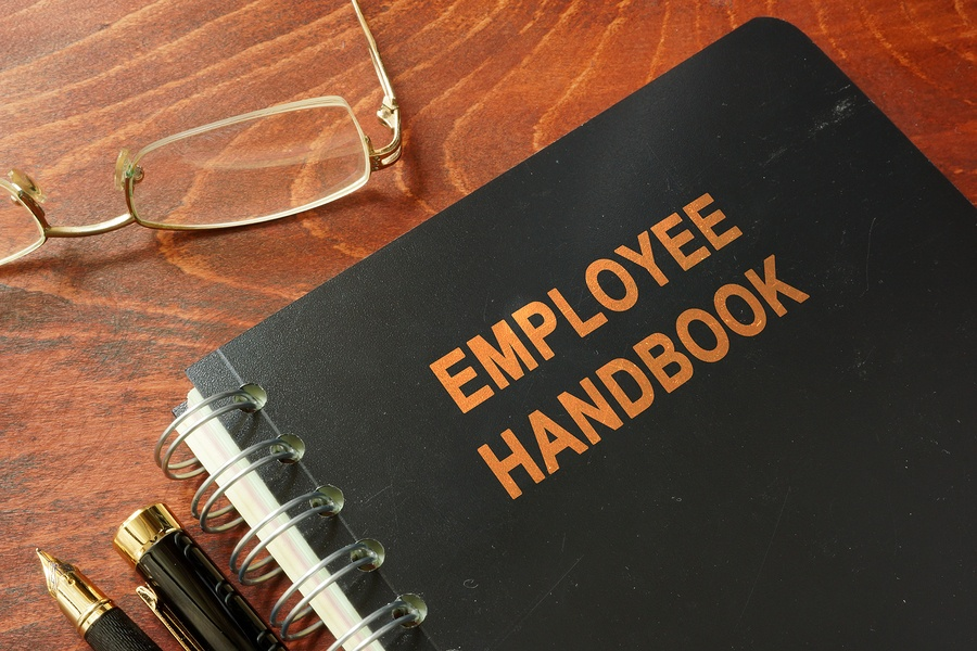 A photo of a spiral bound employee handbook lying on a wood desk.