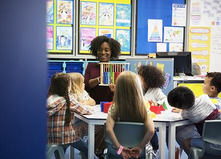A photo of a teacher sitting at a small table with a group of students.