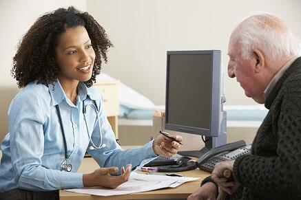Doctor talking about Medicare and employee benefits with an elderly patient.
