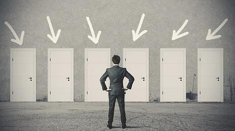 A photo of a man standing in front of six doors, trying to decide which to choose.
