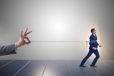 photo image of a hand pulling a rope attached to a business man running away.