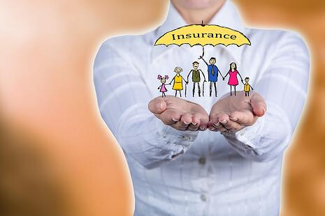 A photo of a woman holding a stick figure family under a life insurance umbrella in her hands.