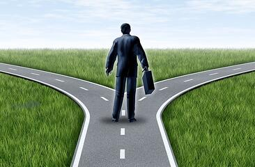 A cartoon image of a man standing at a fork in the road, trying to decide which direction to go.