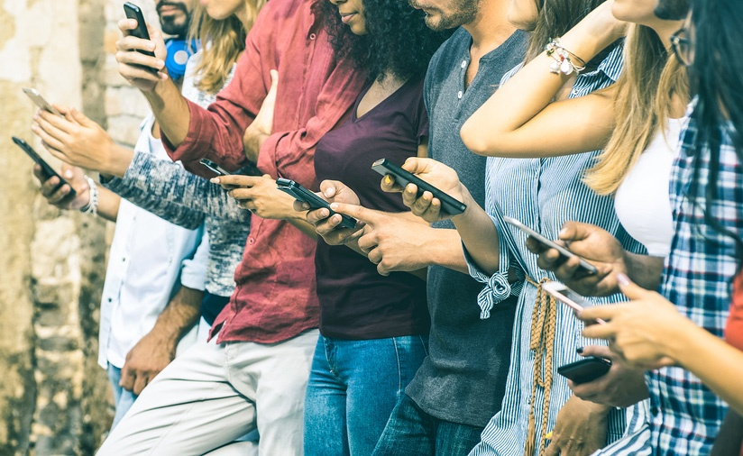 A photo of eight young people in a line, all looking at their smartphones.