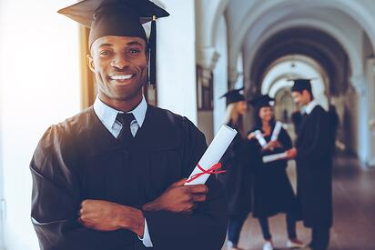 A photo of a man dressed in a cap and gown, holding a rolled diploma.