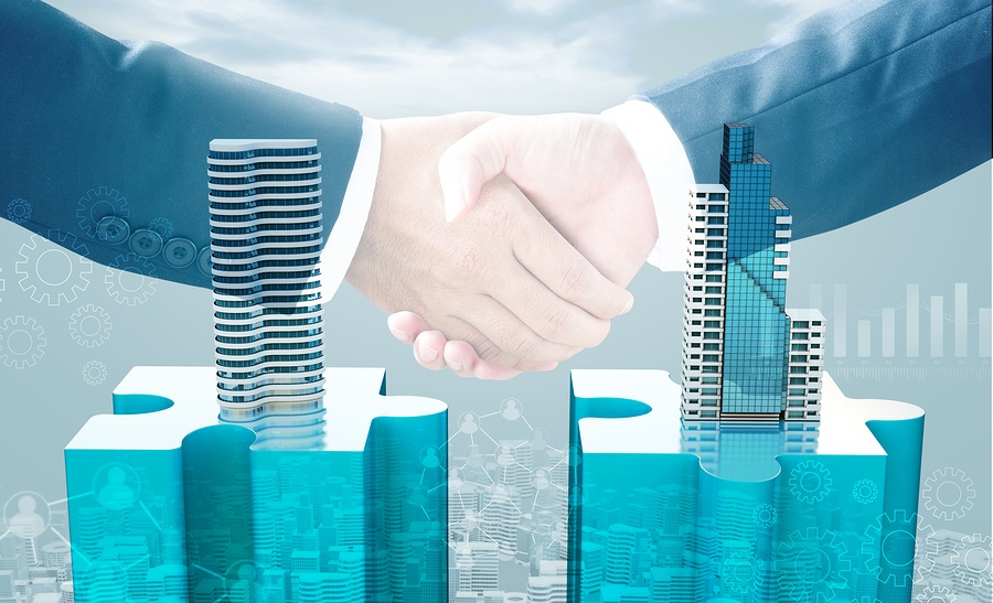 A photo of two hands shaking in agreement above two buildings coming out of puzzle pieces, indicating a successful merger.