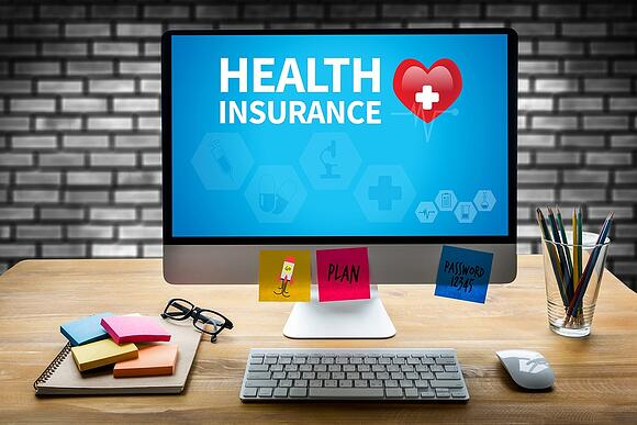 A photo of a desktop computer displaying a health insurance graphic.