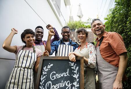 photo of diverse group of people with Grand Opening sign.