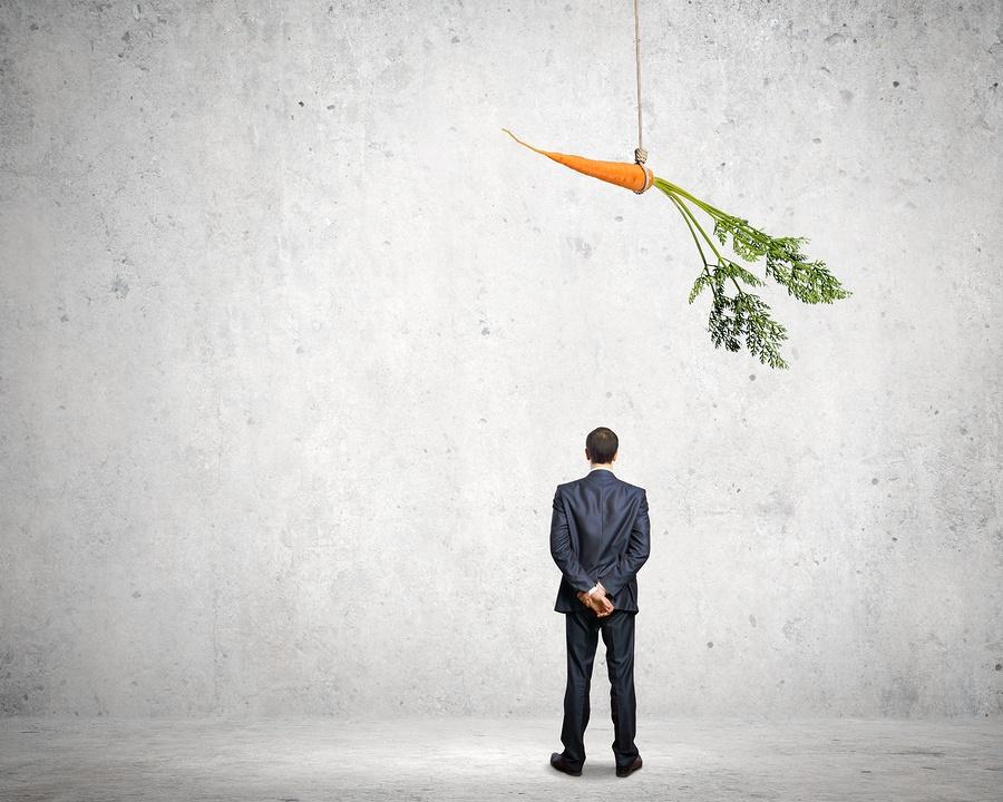 image of a business man facing a dangling carrot.
