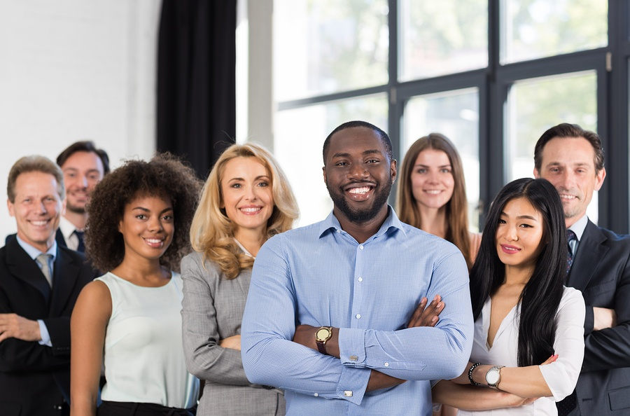 A photo of a diverse group of human resources personnel smiling at the camera.