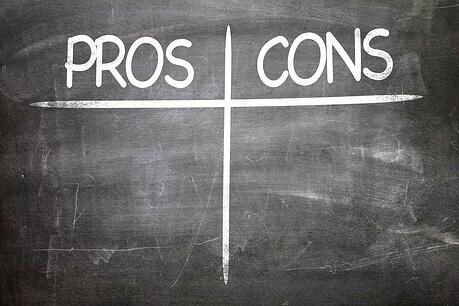 image of a chalkboard with blank pros and cons chart written on it.