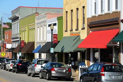 A photo of a row of awnings outside small businesses on a main street in a small town.