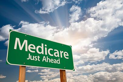 A green road sign indicating Medicare is just ahead.