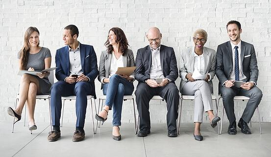 photograph of varied age and gender workforce sitting on chairs.