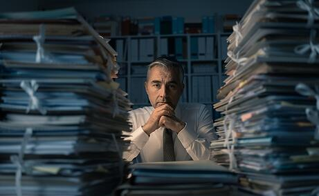 A photo of a man sitting in a darkened office staring at huge stacks of paperwork and file folders.