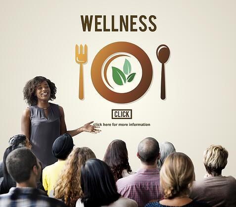 A photo of a woman giving a presentation on wellness to a group of employees.