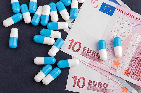 A photo of pharmaceuticals on a table next to european currency.