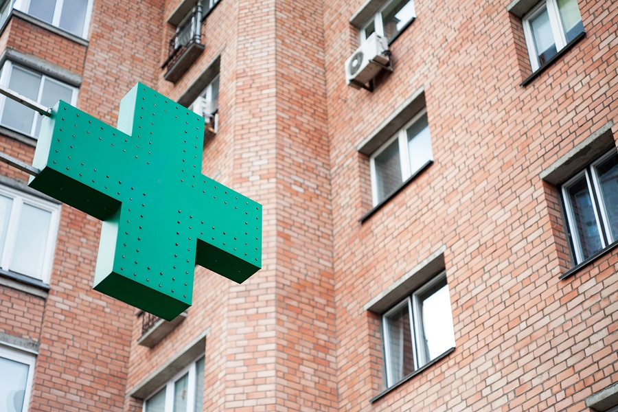 A photo of a green pharmacy sign mounted on the side of a brick building in Europe.