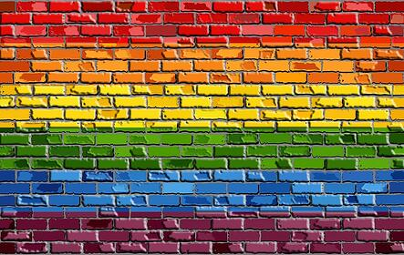 A photo of a brick wall painted to look like a Pride Flag.