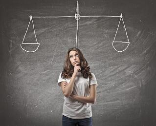 a photo of a woman standing in front of a chalkboard with a tipped scale on it with a thoughtful expression.