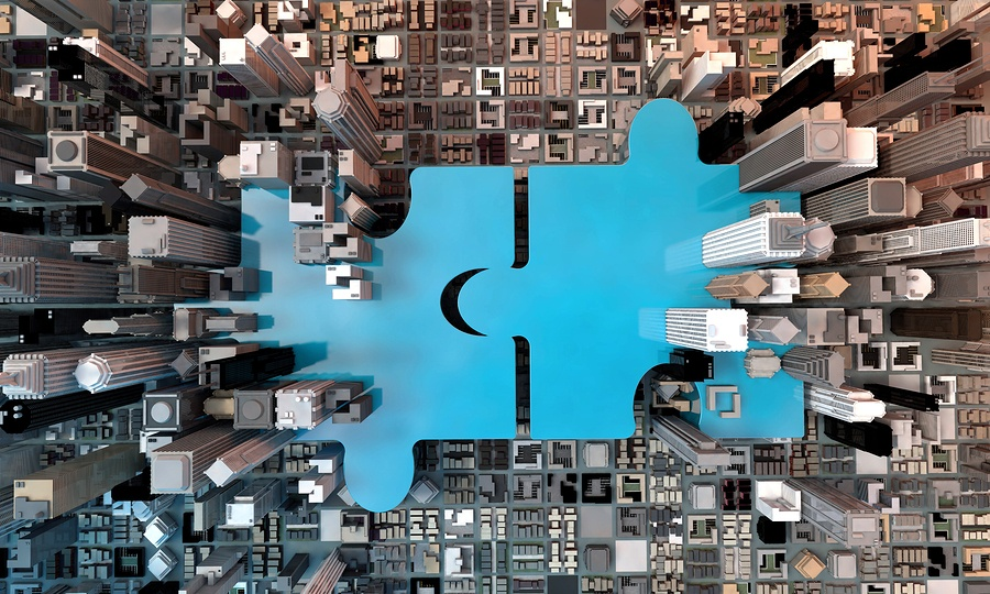 A photo of two blue puzzle pieces coming together amidst tall city buildings.