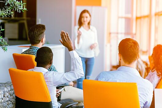 A photo of a man raising his hand to ask a presenter a question in an office.