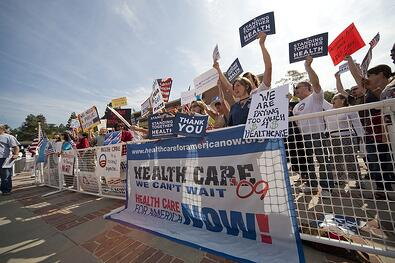 A photo of a group of people gathered for a rally to support healthcare reform.
