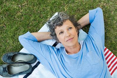 A photo of a retired person lying on a blanket in the grass, looking up to the sky.