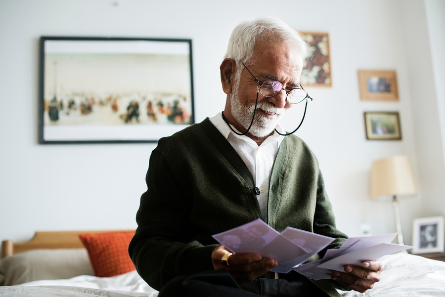 A photo of an older gentleman opening his mail at home.