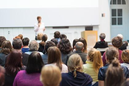 A photo of a woman leading a workplace harassment training seminar.