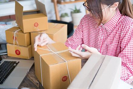 A photo of a woman packing up products to ship to customers.