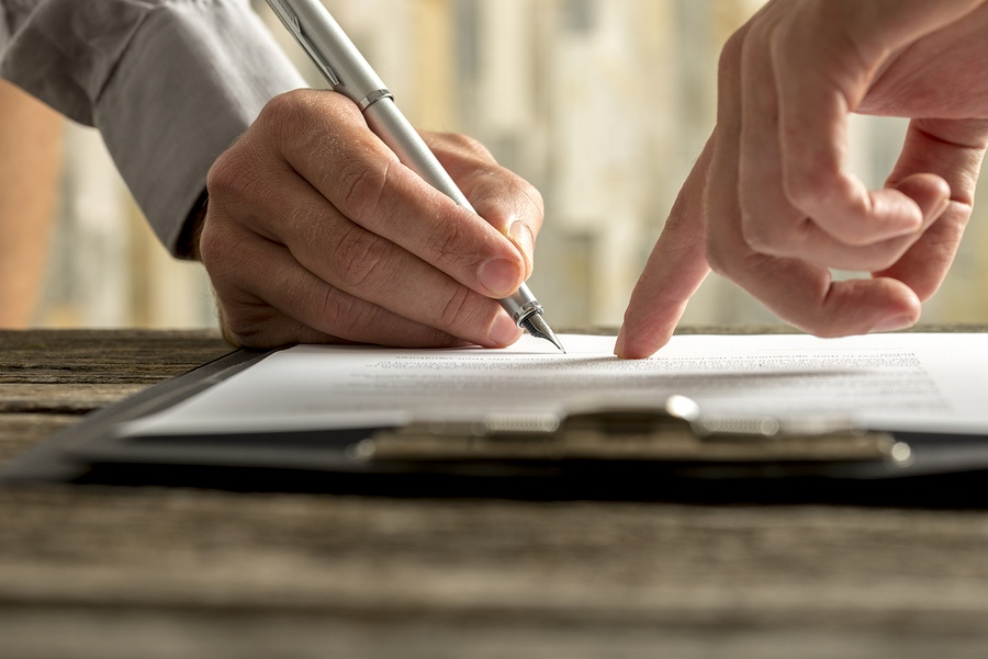 A close up photo of a person pointing to a line on a piece of paper and another person signing where indicated.