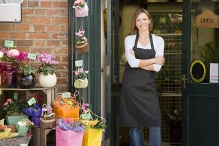 A photo of a small business owner standing outside her flower shop.