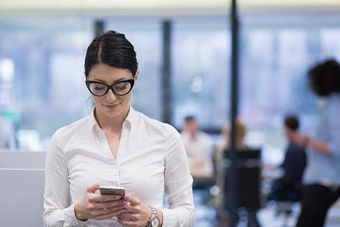 A photo of a woman walking through an office, looking down at her smartphone.