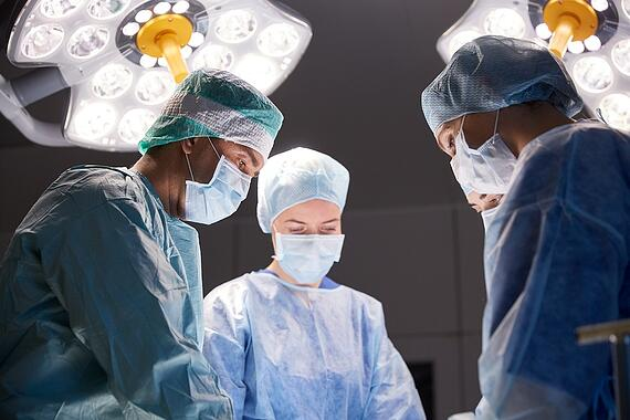 A photo of four surgeons in an operating room with lights shining bright over their heads.