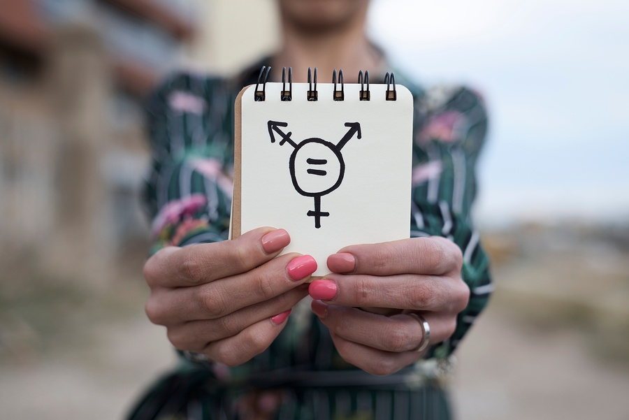 A photo of someone holding up a small notepad with a transgender symbol drawn on it.