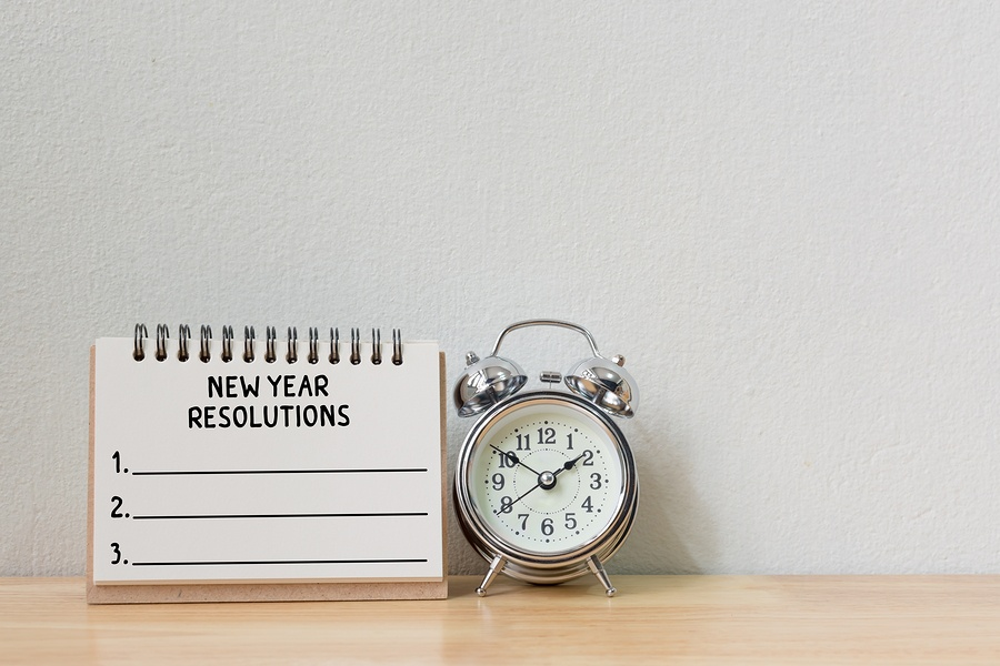 A photo of an alarm clock on a desk with a notepad to write new year's resolutions.