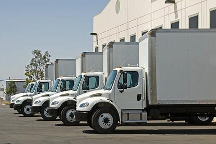A photo of white trucks lined up and waiting to be loaded with product.