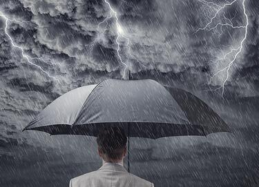 A photo of a man holding an umbrella over his head while a storm rages above him.