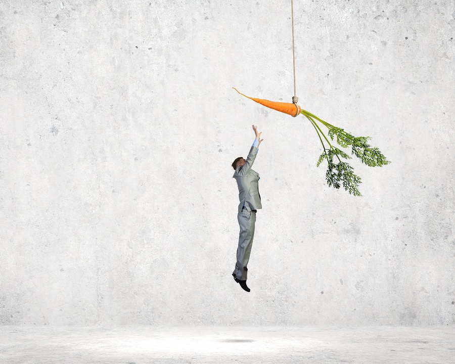 photo of a businessman jumping and reaching for a dangling carrot.