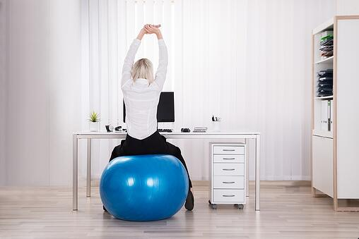 A photo of a woman sitting on a balance ball and stretching at her desk.