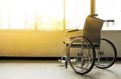 A photo of an empty wheelchair sitting next to window with the sun shining brightly through it.